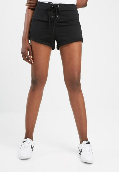 black mini sweat shorts with cuffs, white T-shirt and sneakers