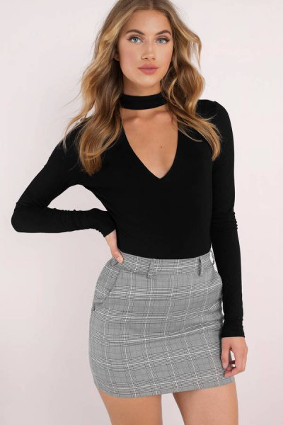 black cut, low-slung long-sleeved top with V-neckline and tweed pencil skirt