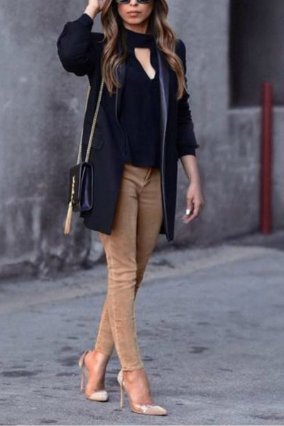 black blouse in front with light brown skinny jeans