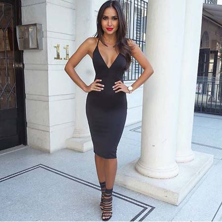 black form-fitting midi dress with deep V-neckline and gladiator sandals