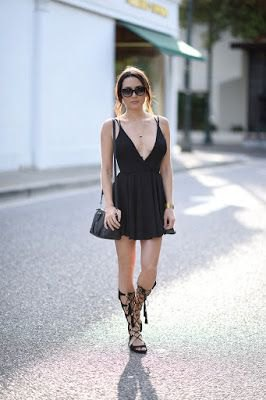 black cocktail dress with deep V-neckline and flare with knee-high strappy sandals