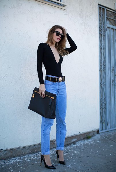 black, low-slung, long-sleeved V-neck t-shirt, blue jeans and cowboy belt