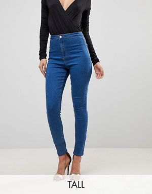 black, deep-fitting, long-sleeved top with V-neckline and blue, tall jeans