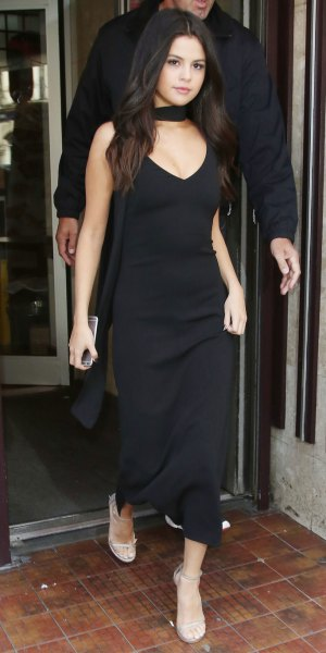 black maxi dress with deep V-neckline and nude sandals