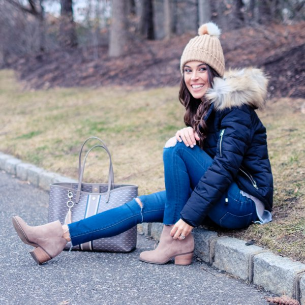 black down jacket with blue skinny jeans and crepe knitted hat