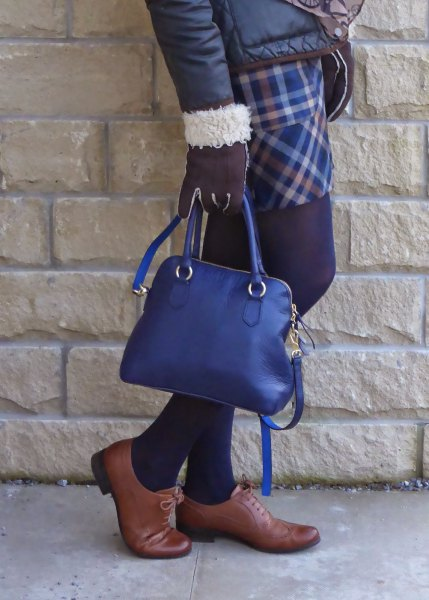 black down jacket with checked skirt and deep blue handbag