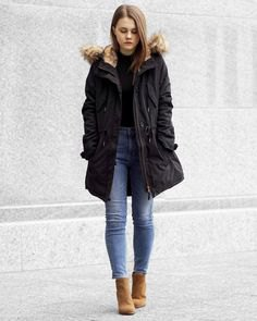 black bomber jacket with hood made of faux fur and slim-fitting ankle blue jeans