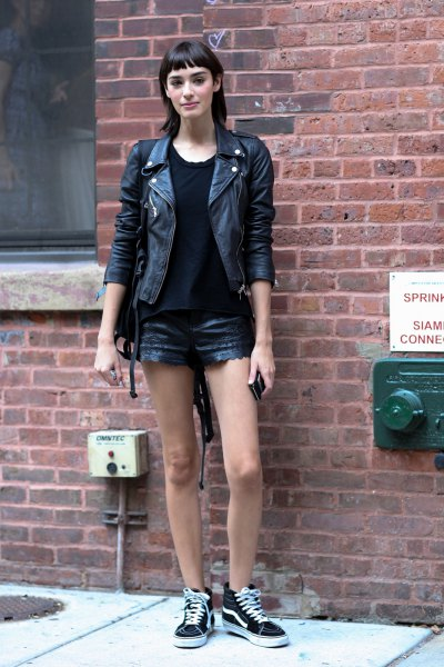black faux leather jacket with mini denim shorts and canvas sneakers