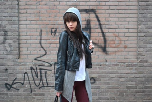 black short jacket made of synthetic leather with a long hooded sweater with zipper