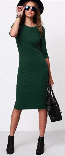 black felt hat with a green midi dress with three-quarter sleeves