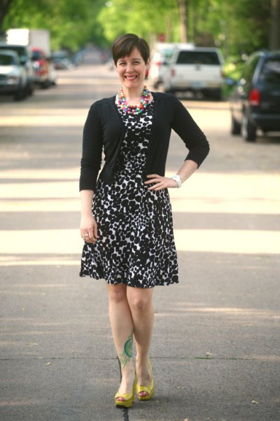 black cardigan with a knee-length, flared dress with leopard print