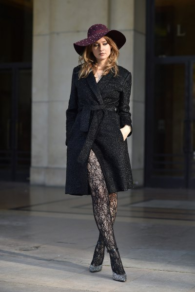 black floppy hat with a long wool coat and tights with a lace pattern