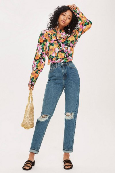 black blouse with floral pattern and blue ripped jeans