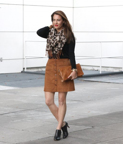 black figure-hugging knitted sweater with brown mini skirt