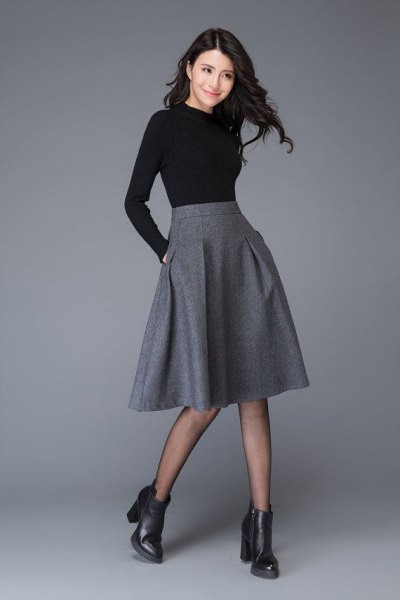 black, figure-hugging long-sleeved T-shirt with midi gray wool skirt