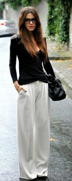 black figure-hugging sweater with scoop neckline and white pants