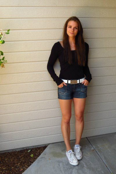black figure-hugging sweater with denim shorts and white belt