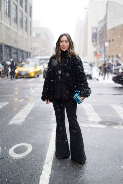 black fuzzy coat with flared jeans and boots with heels
