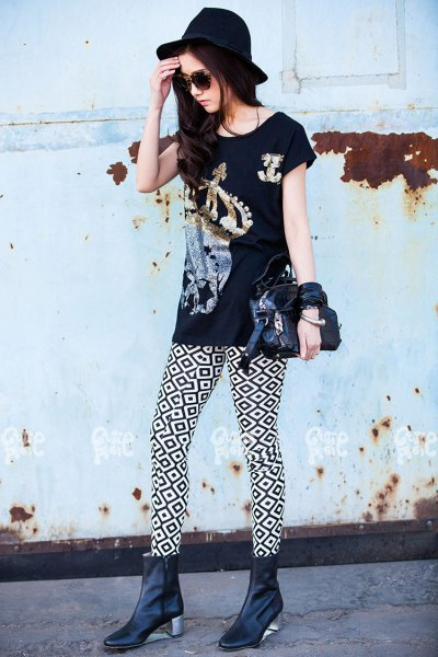 black graphic t-shirt with high-heeled leather boots and a felt hat
