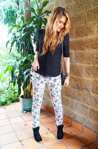 black sweater with half sleeves and white and pink printed pants with a relaxed fit
