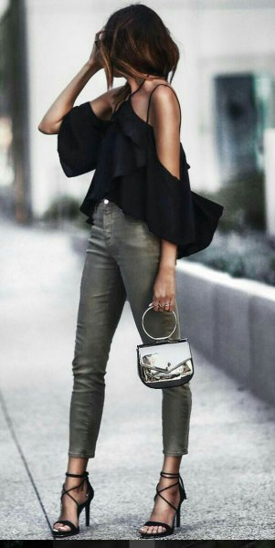 black halterneck blouse with cold shoulder ruffles and gray skinny jeans