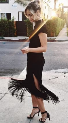 black bodycon dress with high neckline and high, split fringes