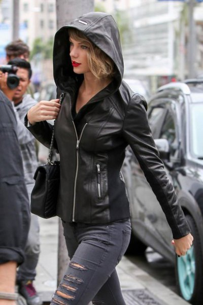 black leather jacket with hood and ripped gray skinny jeans