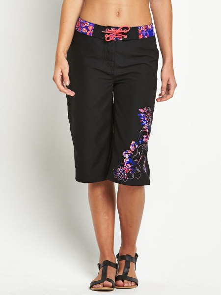 black knee-length board shorts with floral details