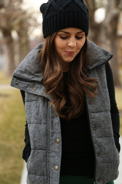 black knitted hat with a gray quilted long vest and knitted sweater