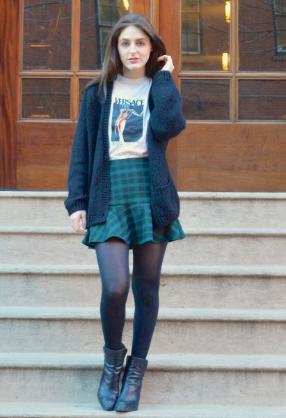 black knitted sweater with white printed t-shirt and dark blue plaid skirt