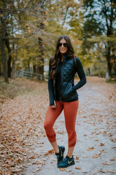 black down vest made of leather with fitted sweater and green leggings