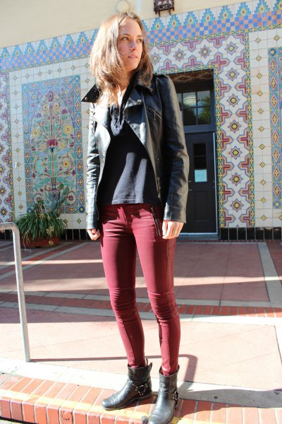 black leather jacket with green coated skinny jeans