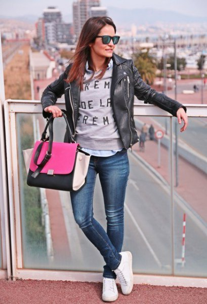 black leather jacket with gray graphic sweater and white tennis shoes