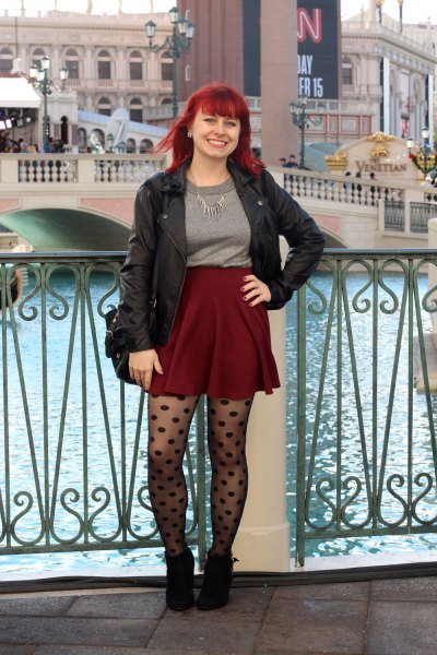 black leather jacket with gray sweater and burgundy mini skirt