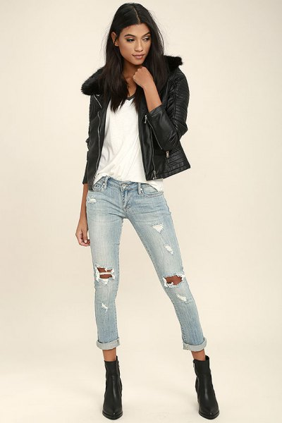 black leather jacket with a white t-shirt with a scoop neckline and light gray jeans with a tear