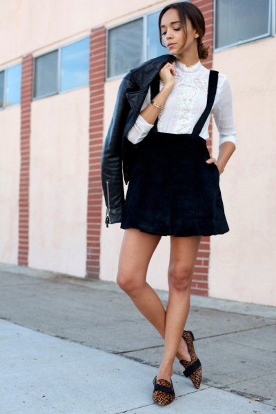 black leather jacket with white shirt and suspender skirt