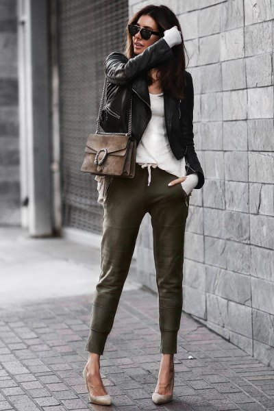 black leather jacket with white top and khaki joggers