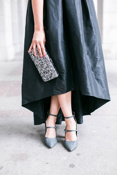 black maxi dress made of leather with a silver clutch made of sequins