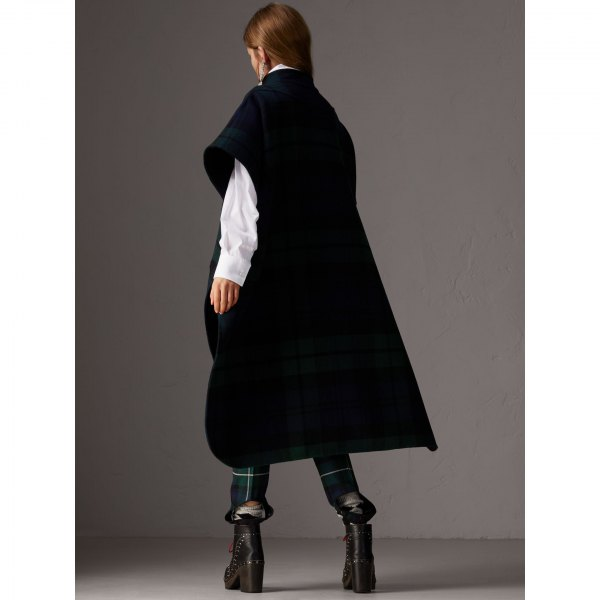 black long poncho over white checked shirt trousers