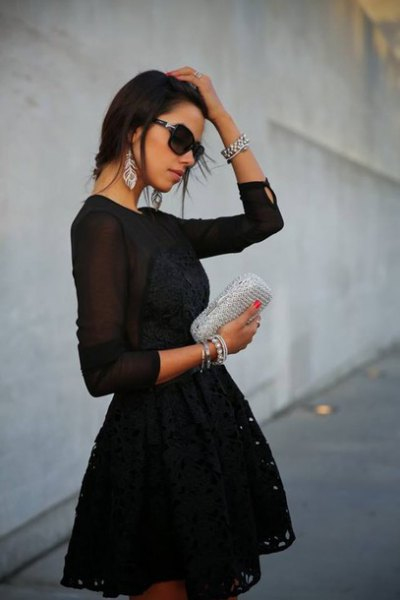 black long-sleeved mini dress made of chiffon with a fit and flare with a silver clutch wallet