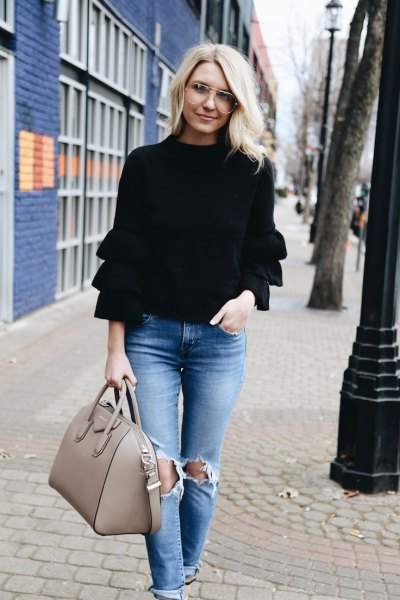 black long-sleeved ruffle sweater with ripped jeans