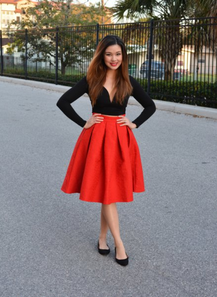 black long-sleeved sweat style top, red flared pleated skirt