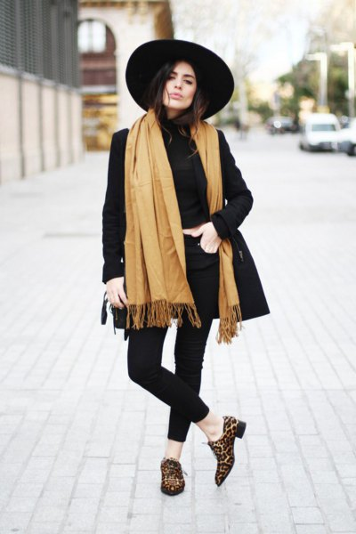 black longline blazer with an orange fringed scarf and slippers with a leopard print