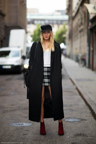 black maxi coat with white sweater and checked mini skirt