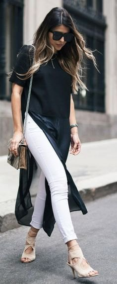 black maxi short-sleeved blouse with high slit and white jeans with cuffs