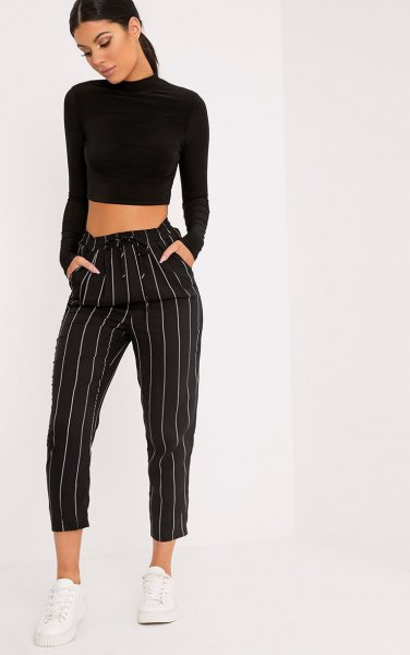black, cropped sweater with stand-up collar and striped, cropped pants with wide legs