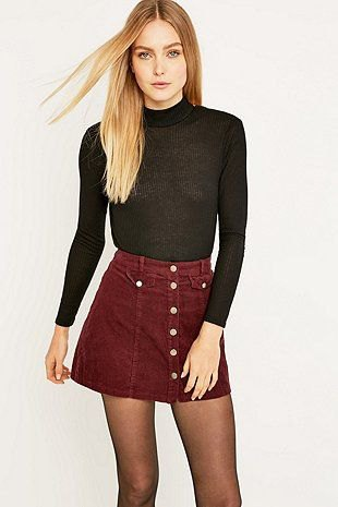 black, figure-hugging sweater with stand-up collar and burgundy-colored mini skirt with button placket at the front