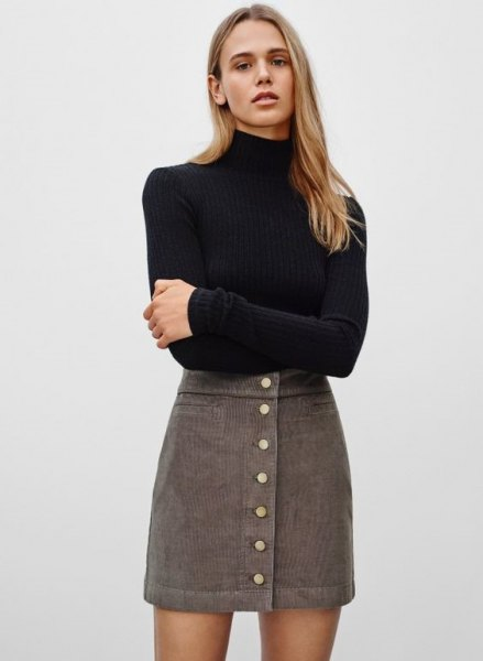 black, figure-hugging sweater with stand-up collar and gray, high-waisted mini-cord skirt