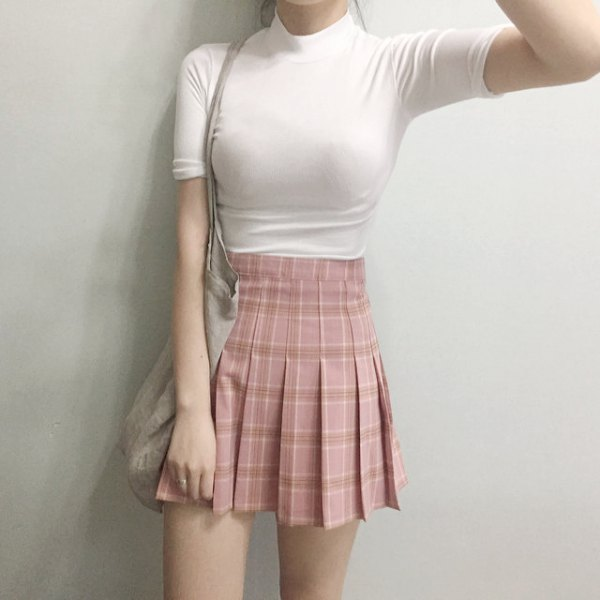 black, figure-hugging T-shirt with stand-up collar and pink pleated mini skirt with high waist