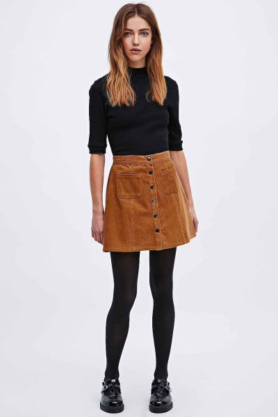 black mock-neck sweater with half sleeves and brown corduroy mini skirt